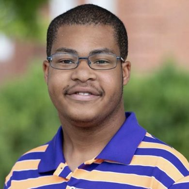 Headshot of youth leader, Jonathan, male with black hair and glasses, smiling and wearing a purple and yellow striped polo shirt